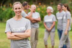 Happy volunteer looking at camera with arms crossed - stock photo