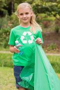 Stock Photo of Happy little girl collecting rubbish