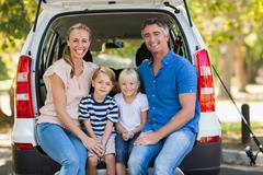 Happy family of four sitting in car trunk Stock Photos