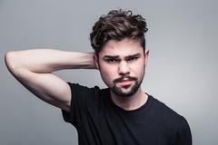 Young man in  black T-shirt doubting - stock photo
