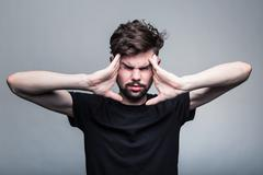 Young man is experiencing intense headache - stock photo
