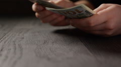 Young female hands count dollar bills on wooden table, prores hq footage Stock Footage