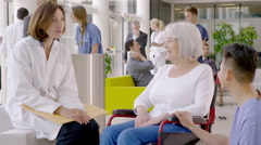 4K Caring medical staff talking to patient in wheelchair in busy modern hospital Stock Footage