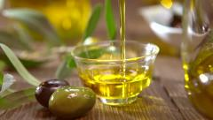 Olives and pouring olive oil. Extra virgin olive oil pouring from a jar Stock Footage