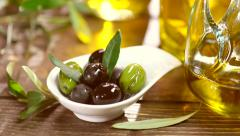 Olives. Green and black olives closeup. Olive oil on the wooden table Stock Footage