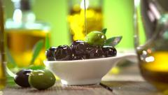 Olives and pouring olive oil. Extra virgin olive oil pouring from the bottle - stock footage