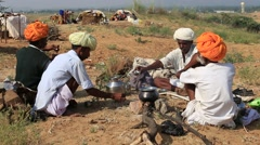 Indian men prepare a meal on a campfire during Pushkar Camel Mela. India Stock Footage