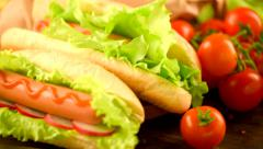 Hot dog. Grilled hot dogs with mustard and ketchup on a picnic wooden table Stock Footage