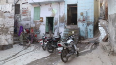 Traditional women and parked motorcycles in front of house in small alley. Stock Footage