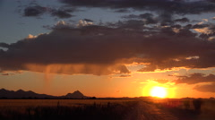 4K Rain Shafts Sweep Silhouetted Landscape At Sunset Time Lapse Stock Footage