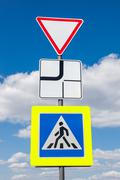 Traffic signs main road and pedestrian crossing with clouds in background Stock Photos
