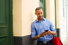 African American Man Shopping And Text Messaging On Phone Stock Photos