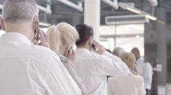 4K Business people on mobile phones as they wait in queue at airline security - stock footage