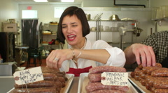 2 Butchers arranging sausages and meats for sale in shop - stock footage