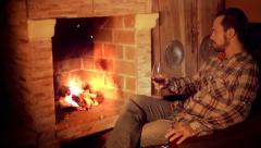 Man drinks red wine in front of fireplace Stock Footage