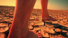 Barefoot woman walks through surreal desert land landscape Stock Footage