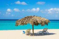 Tropical beach, sunbeds and palm tree umbrellas Stock Photos