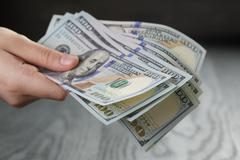 female hand hold bunch of dollars, closeup - stock photo