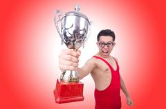 Funny wrestler with winners cup on red Kuvituskuvat