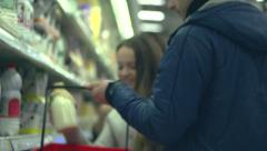 Family of mother father and teenage daughter choosing milk bottle in supermarket - stock footage