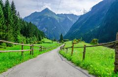 High peaks of the Alps with coutry road,  Austria Stock Photos