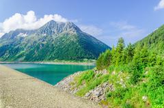 Dam and azure mountain lake  Alps, Austria - stock photo