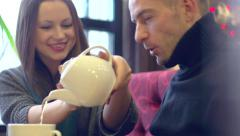 Beauty woman holding teapot and pouring beverage in cups. Smiling couple in cafe Stock Footage
