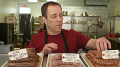 A butcher arranging sausages to sell in a butcher shop - stock footage