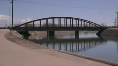 Desert Water Canal 03 with traffic bridge in background Stock Footage