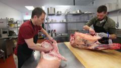 Butchers trimming cow and pig in a butcher store Stock Footage