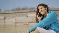 Pretty woman on the beach talks on her phone in slow motion - stock footage