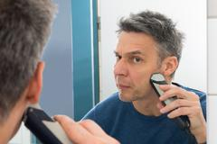Portrait Of A Man Looking In Mirror Trimming Beard - stock photo
