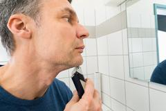 Portrait Of A Man Looking In Mirror Trimming Beard Stock Photos