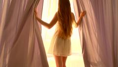 Girl opens curtains on big window and lets the light into the room Stock Footage