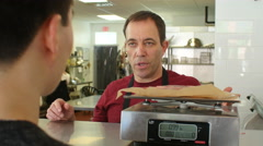 Butcher weighing meat for a customer Stock Footage