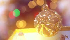 Opening a Christmas golden gift box with a blinking bauble inside - stock footage