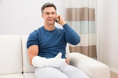 Man With Fractured Hand Sitting On Sofa Talking On Cellphone - stock photo