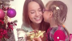 Young smiling mother presents a Christmas gift box to her little daughter - stock footage