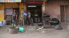 Indian man and two boys working in front of a workshop in Jodhpur. Stock Footage