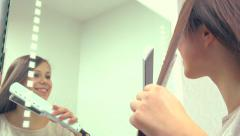 Young attractive woman ironing her hair Stock Footage