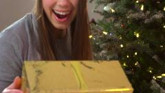 Beauty girl in santas hat looking at her Christmas gift bo Stock Footage