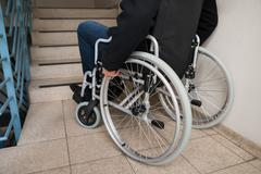 Close-up Of Disabled Man On Wheelchair In Front Of Staircase - stock photo