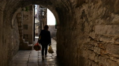 Woman walking with the bike in the narrow streets of the old town in Split Stock Footage