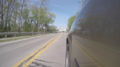 Bridge Reflected in Side of Vehicle as it drives Stock Footage