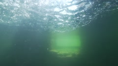 Sunlight penetrates the water and illuminate underwater stone wall in lake Stock Footage