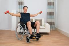 Handicapped Man On Wheelchair Working Out With Dumbbell At Home Stock Photos