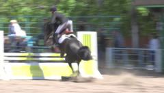 Jumping horse through the barrier on equestrian competitions at arena Stock Footage