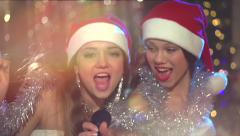 Christmas karaoke party. Two beautiful teenage girls in santas hats singing Stock Footage