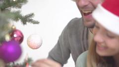 Happy couple in santa hats decorating tree Stock Footage