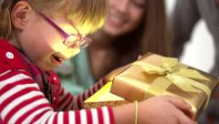Young parents presenting a gift box to their daughter under a christmas tree Stock Footage